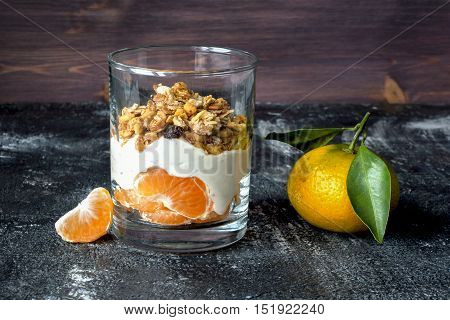 Parfait with yogurt, mandarin fruit pieces and muesli on dark table.