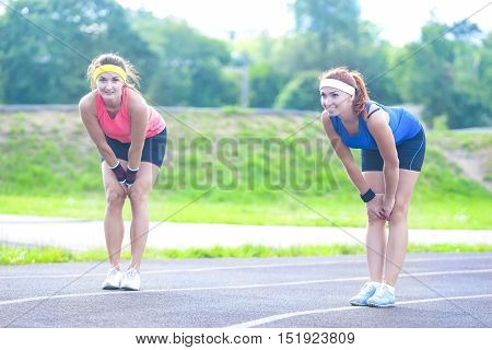 Jogging and Fitness Concepts. Two Female Runners Standing on Lines Prior to Training Start off. Horizontal Image