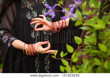 Woman hands in black dress with bracelets gesturing in Indian style in garden