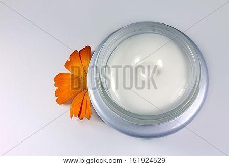 Glass jar of moisturizing face cream and calendula flower