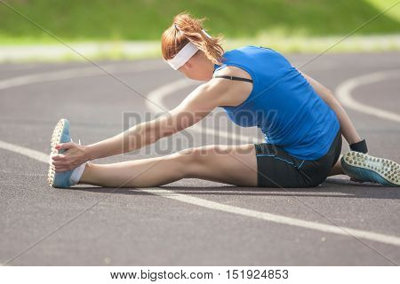 Sport and Athletics Concepts and Ideas. Caucasian Female Sportswoman Having Legs Muscles Stretching Exercises Outdoors. Horizontal Image