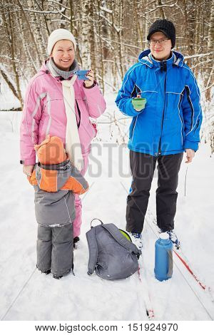 Smiling mother and father with cups of hot tea and little kid in winter snowy park during ski tour.