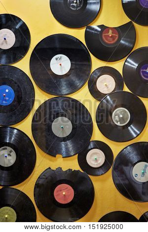 Old dusty damaged vinyl disks pinned to the yellow wall.
