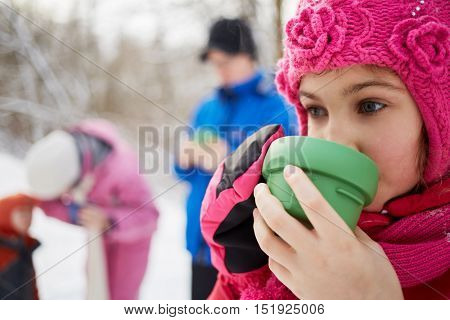 Close-up girl drinking tea from plastic cup in winter cold day. Mother, father and kid out of focus.