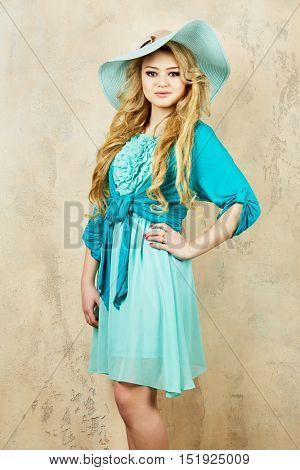 Portrait of young blonde woman in cyan dress and wide-brimmed hat at wall in studio.