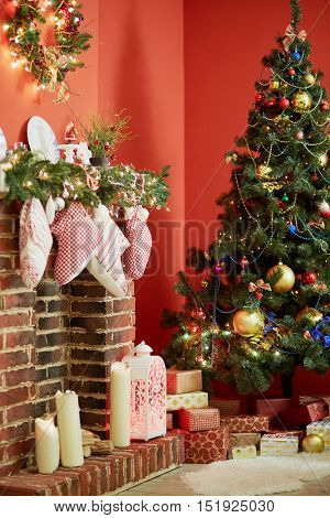 Room with firtree decorated to christmas holidays, fireplace, red walls.