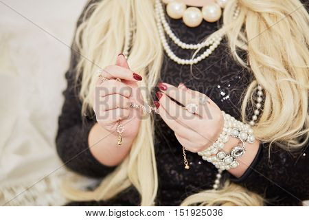 Blonde woman in dark dress holds jewelry in hands.
