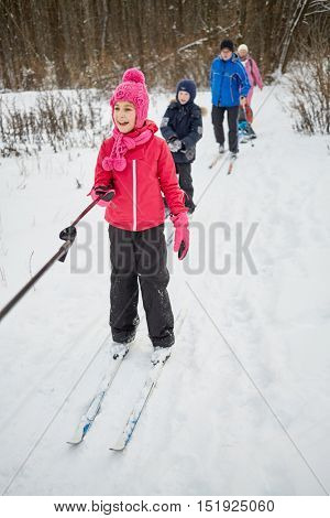 Girl and boy slide on skis in park pulled by ski-pole in chain. Man and woman slide behind them. Focus on girl.