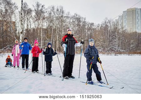 Group of seven people three adults and four children slide on skis and sledge across snowy lawn.