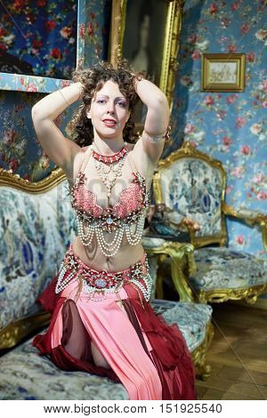 Woman dressed in oriental costume poses sitting on sofa in old-fashioned style room.