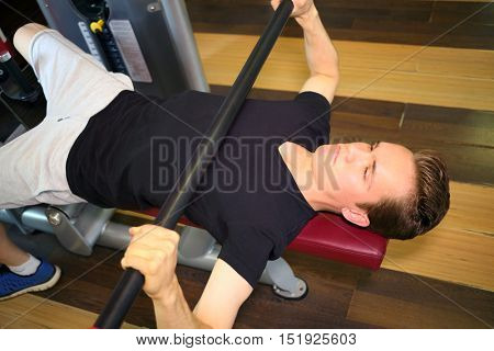 Man lying and pushing steel bar in fitness room alone, top view