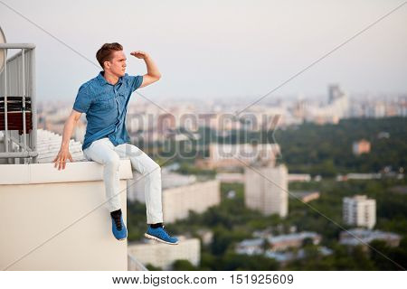 Young man in denim clothes looks afar, sitting on the edge of the roof and having put a hand as a peak to a forehead.