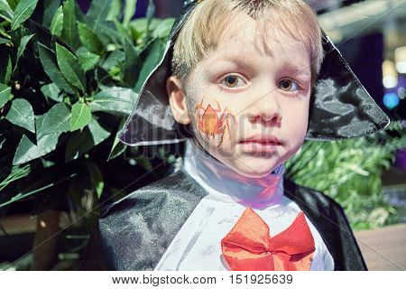 Closeup portrait of little boy dressed in carnival costume in front of bush with green leaves.