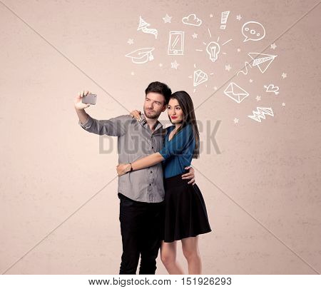A young couple in love taking selfie with a mobile phone in the handsome guy's hand and drawn media communication icons above them, confused ideas concept