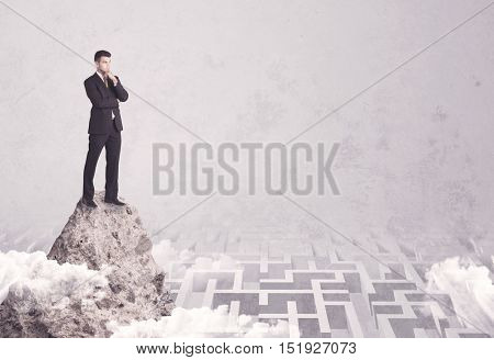 Maze is no challenge for successful businessman standing on top of a cliff as he is the best at solving problems concept