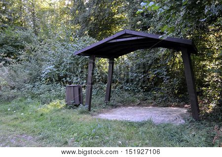 Wooden shelters with a trash can along a forest in Belgium.