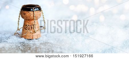 New Year background 2017 with a champagne cork in the snow and bokeh