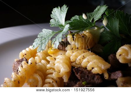 Dish with beef, fusili pasta and leaf parsley.