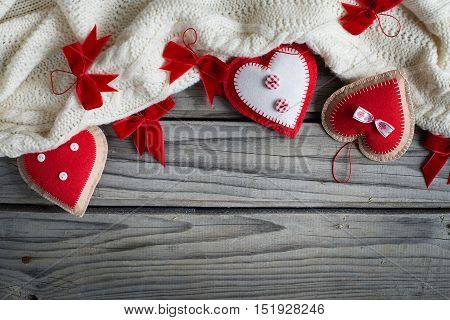 Red handmade heart and white scarf on a wood background.