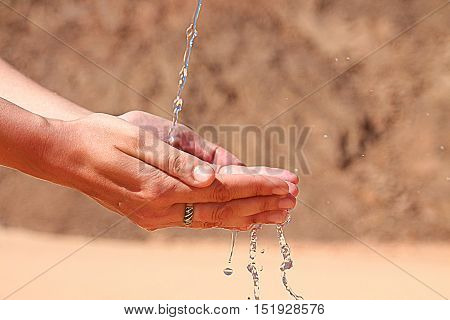 Woman's hands with water. Thirsting in desert