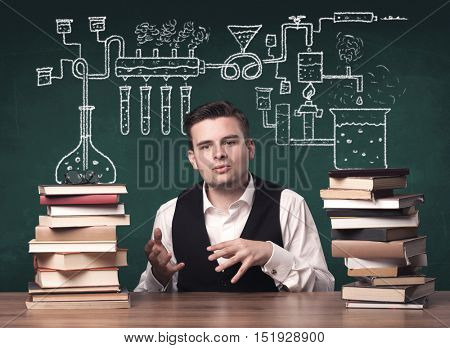A young chemistry teacher in the middle of a chemical process explanation with tubes, reactions drawn on the blackboard back to school concept.