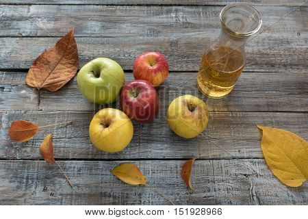 Apple cider in bottle and fresh apples on wooden background.Autumn concept