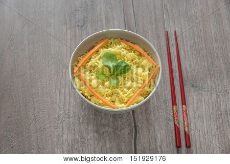Bright yellow boiled rice with turmeric and aromatic spices on a bright wooden background