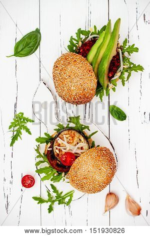 Fresh homemade two veggies burgers served on cutting board over white rustic table. Vegan grilled eggplant arugula sprouts and pesto sauce burger. Veggie beet and quinoa burger with avocado. Top view overhead flat lay