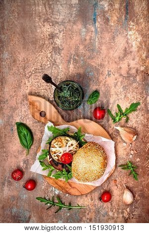 Fresh homemade two veggies burgers served on cutting board over stone vintage background. Vegan grilled eggplant arugula sprouts and pesto sauce burger. Veggie beet and quinoa burger. Top view overhead flat lay. Copy space
