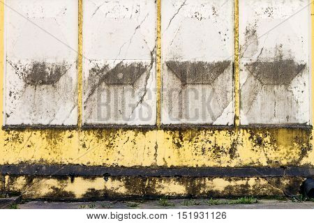 Aged weathered cracked yellow concrete fence background