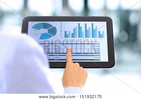 The young businesswoman showing graphs by finger at the digital tablet