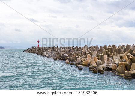 Lighthouse sea coastline with massive group of breakwater.