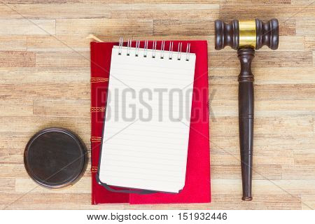 Wooden Law Gavel, empty notebook and legal book on wooden table