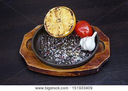Grilled lemon tomato and garlic with herbs in a cast iron frying pan on a wooden stand