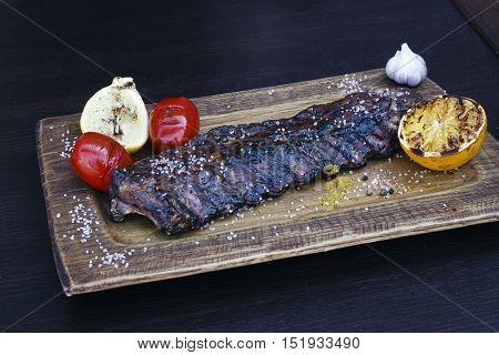 pork ribs grilled with tomatoes lemon and garlic on a wooden plate