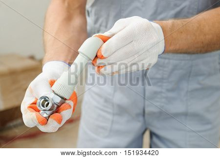 Soldering plastic pipe. A worker holds the valve and soldered pipe and knee.