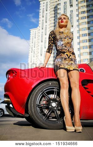 MOSCOW - SEP 13, 2015: Woman (with model release) poses near Lotus cabriolet car. Lotus Cars - British manufacturer of sports and racing cars
