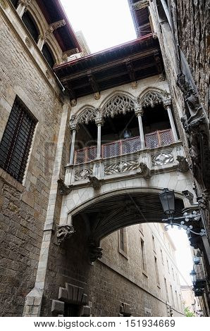 Tiny balcony connecting two buildings in old city part of Barcelona, summer Spain