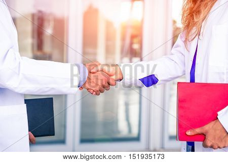Doctors handshake with white coat holding folders at hospital room entrance - Physician professional business meeting inside clinic hand gesture close up - Concept of team working in medical world