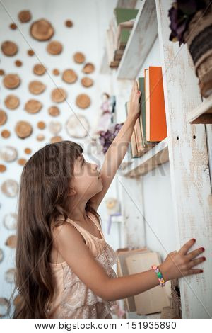 small kid searching book interesting fairy tale near bookcase;