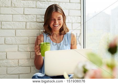 Close-up of young modern girl who is laughing softly sitting on the window-sill and working on her laptop