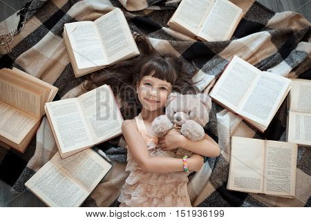Cheerful Little Girl Lying On Floor With Lot Of Books;