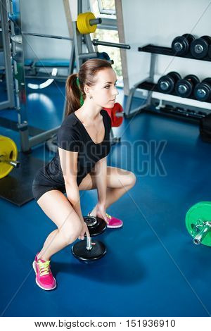 Long hail girl doing squats with a dumbbell.