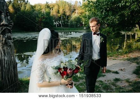 young bridal couple posing on a background of lake