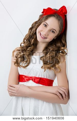 Beautiful teenage girl with long curly hair and red ribbon bow on head wearing white dress. Happy expression. Studio portrait on white background. Copy space.