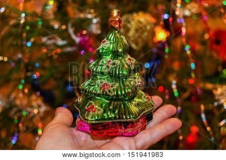 Glass vintage toy green Christmas tree on the open palm of hand on a colorful background with bokeh.