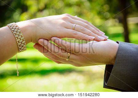 hands of Bridal couple with wedding rings on a green background