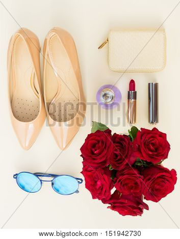 Nude colored high heels still life with wallet, roses, sun glasses and red lipstick, top view