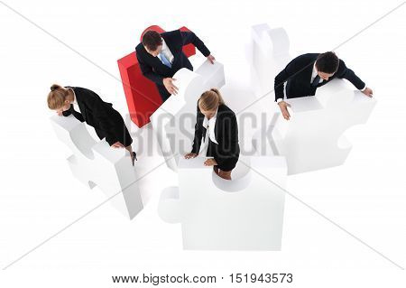 Business people team assembling puzzle isolated on white background