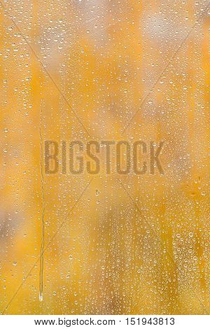 Natural water drops on window glass with a yellow background